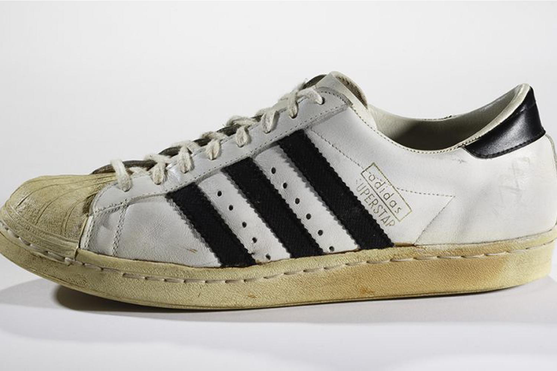 Adidas Stan Smith puis Superstar : au cours des années 1960, Adidas développe une chaussure de tennis avec le tennisman français Robert Haillet, également directeur commercial de la marque. Cette paire possède une semelle vulcanisée avec un motif à chevrons moulé pour plus d'adhérence sur le court, des perforations sur la tige (partie qui recouvre le pied), mais c'est sa composition en cuir qui la rend réellement exceptionnelle. Première sneaker en cette matière, elle devient légendaire lorsque Adidas signe un contrat en 1973 avec le tennisman californien Stanley Smith, meilleur joueur du monde à l'époque (vainqueur de l'US Open 1971 et de Wimbledon 1972). La chaussure est ainsi rebaptisée Adidas Stan Smith en 1978 avant de devenir, dans les années 1980, un véritable modèle culte. Portée autant sur les courts de tennis que dans les rues, l'Adidas Stan Smith est l'une des premières paires (sinon la première) à être portée en dehors de toute activité sportive. Sa nouvelle version dite Superstar s'érige au rang d'icône dans la culture hip-hop dans les années 1980 grâce à des émissions comme Graffiti Rock. La Superstar, c'est toute une époque qui transpire et qui se réapproprie le modèle. C'est aussi bien les B-boys qui dansent avec leurs imposants lacets que les grandes figures de la culture urbaine comme les rappeurs Run DMC qui s'exhibent avec leurs vestes en cuir, leurs pantalons noirs et leurs paires de baskets sans lacets pour rappeler la prison.